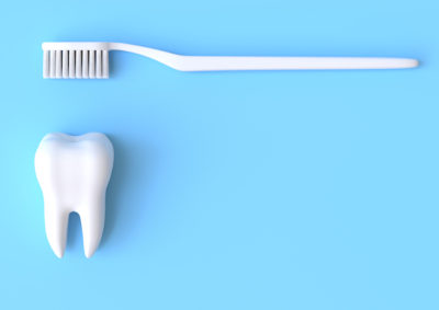 Toothbrush and white tooth on a blue background