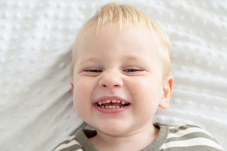 baby smiling and showing their teeth